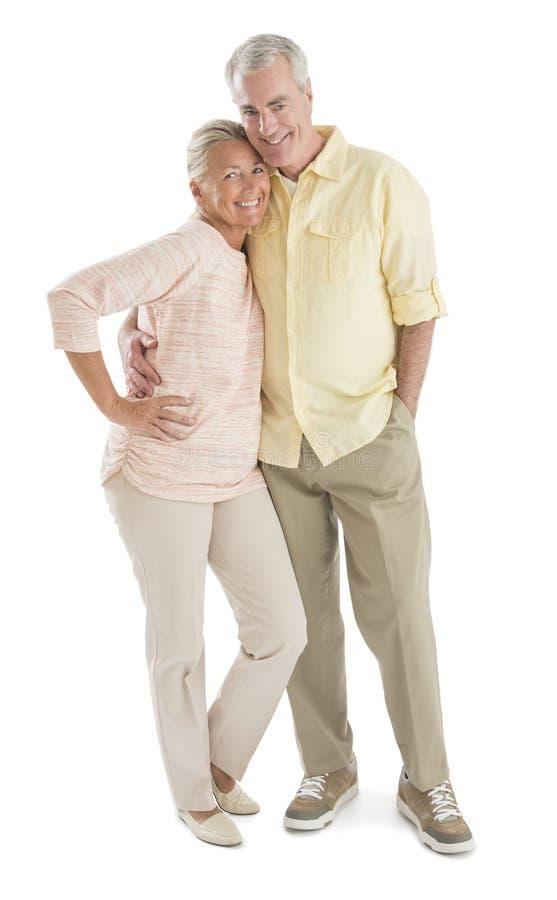 Liebevolle ältere Paare gegen weißen Hintergrund lizenzfreie stockbilder