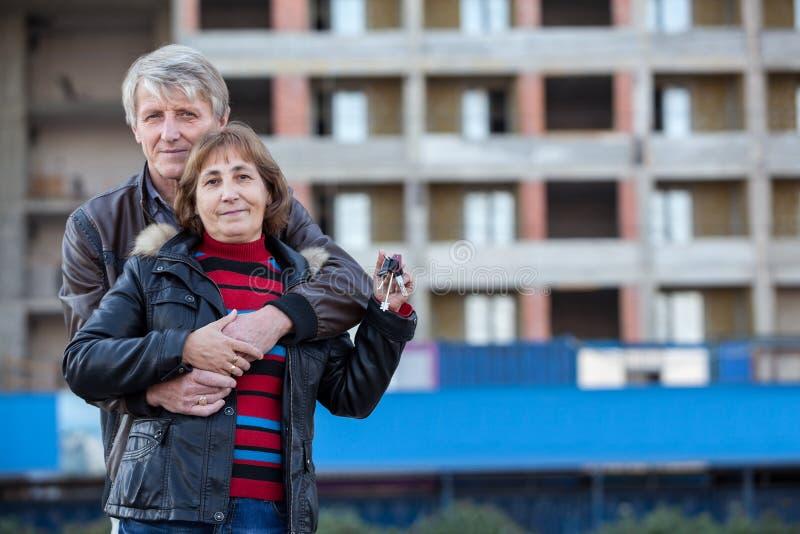 Liebevolle ältere Paare mit Hausschlüssel in der Hand umfassen, copyspace lizenzfreies stockfoto