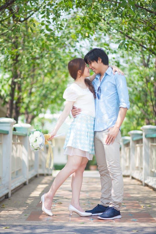 Liebevolle asiatische Paare unter Baum stockfotos