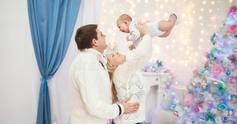 Liebevolle Eltern spielen mit dem Kind, das vor dem Weihnachtsbaum steht lizenzfreies stockbild