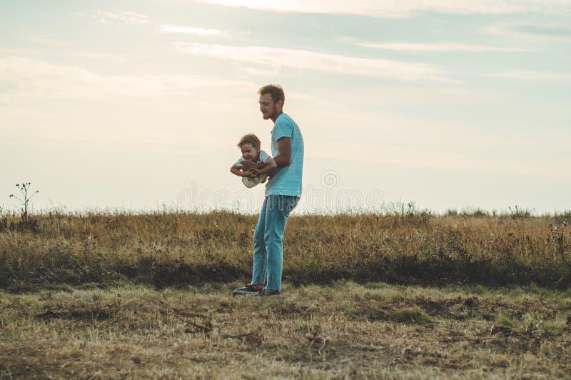 Liebevolle Familie Bringen Sie und sein Sohnbaby hervor, das draußen spielt und umarmt Glücklicher Vati und Sohn draußen Konzept  lizenzfreie stockfotografie