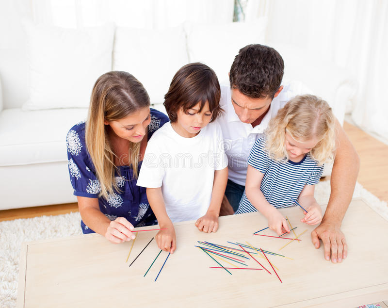 Liebevolle Familie, die mikado im Wohnzimmer spielt lizenzfreie stockfotografie