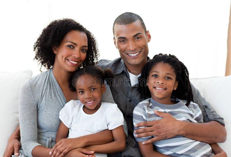 Liebevolle Familie, die zusammen auf dem Sofa sitzt lizenzfreie stockfotografie