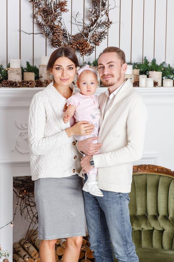 Liebevolle Familie frohe Weihnachten und guten Rutsch ins Neue Jahr Nette hübsche Leute Mutter und Vati, die kleine Tochter umarm lizenzfreies stockfoto
