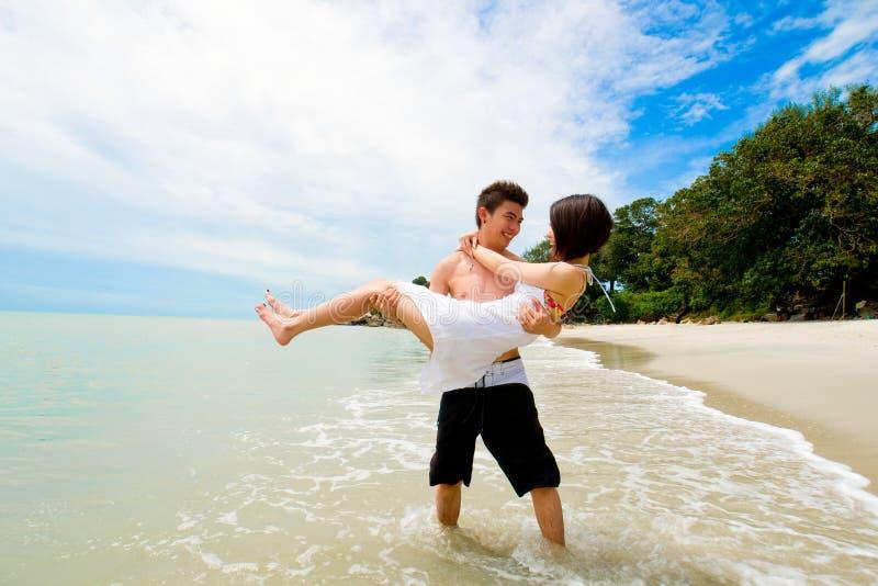 Liebevolle glückliche Paare am Strand lizenzfreie stockbilder