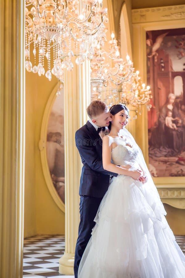 Liebevolle Hochzeitspaare, die in der Kirche umfassen lizenzfreie stockfotos