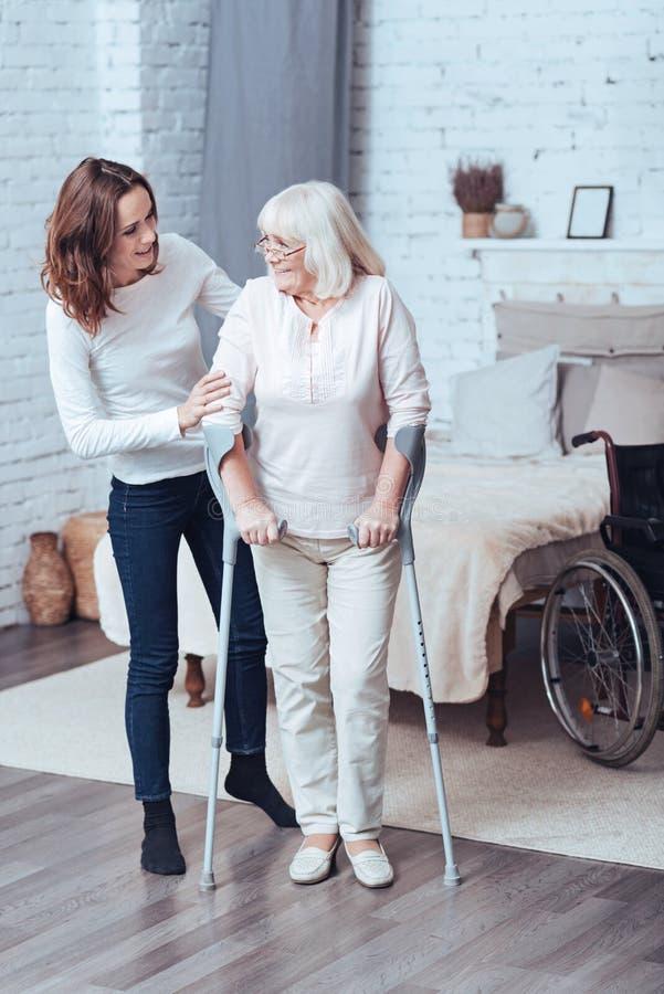 Liebevolle junge Frau, die zu Hause arbeitsunfähiger alter Dame hilft stockfotografie