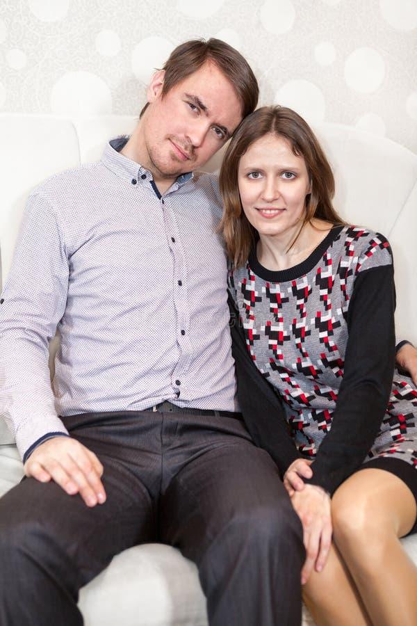 Liebevolle junge kaukasische Paare, die zusammen auf Sofa sitzen lizenzfreie stockbilder
