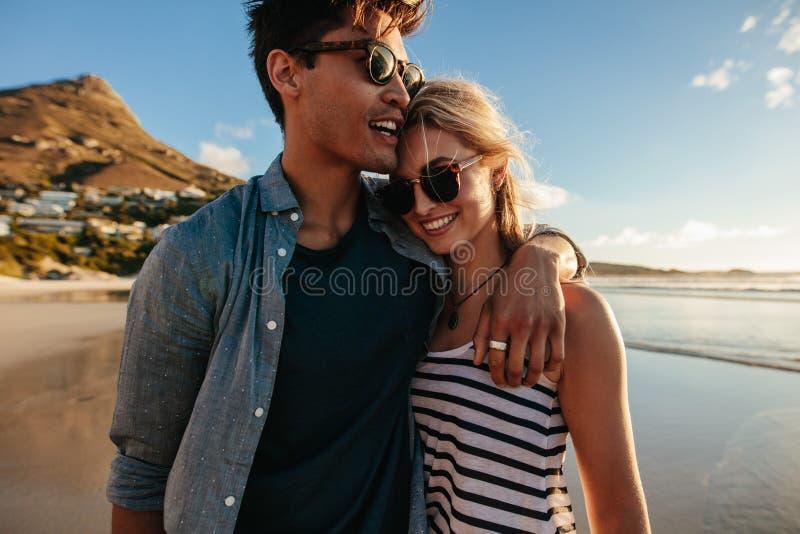 Liebevolle junge Paare, die auf Strand gehen lizenzfreie stockfotos