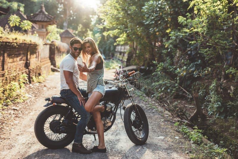 Liebevolle junge Paare, die ein selfie mit Motorrad nehmen stockfotografie