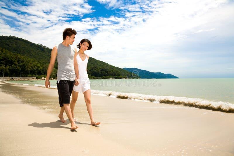 Liebevolle junge Paare, die entlang den Strand gehen lizenzfreie stockbilder