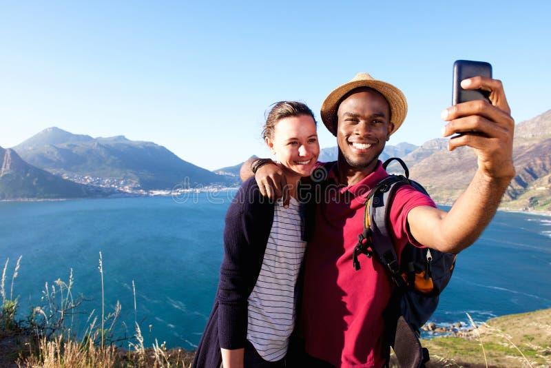Liebevolle junge Paare am Feiertag selfie nehmend stockbild