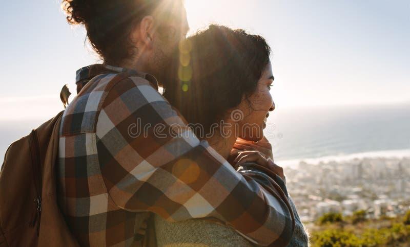 Liebevolle junge Paare, welche die Ansicht bewundern stockfoto