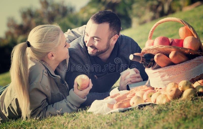 Liebevolle junge schöne Paare, die plaudern als, Picknick habend stockfoto