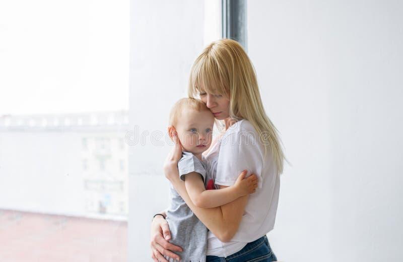 Liebevolle Mutter, die für ihr Baby sich interessiert lizenzfreie stockfotos