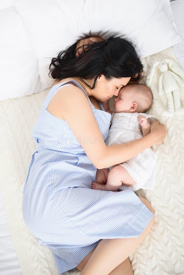 Liebevolle Mutter, die für ihr Baby sich interessiert stockfoto