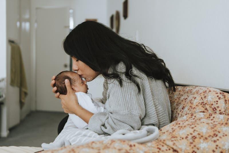 Liebevolle Mutter, die ihr Säuglingsbaby küsst lizenzfreies stockfoto