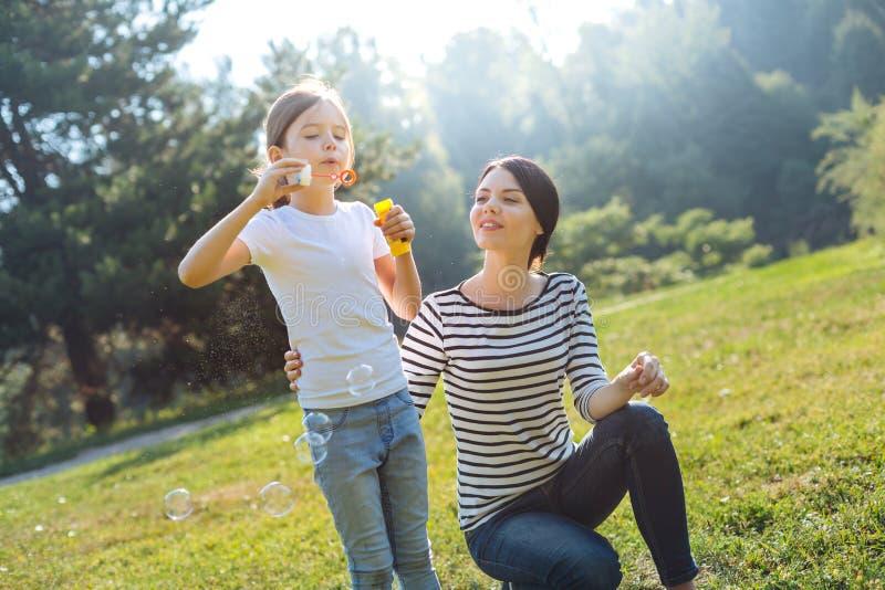 Liebevolle Mutter, die ihr Tochterspiel mit Seifenblasen aufpasst stockfoto