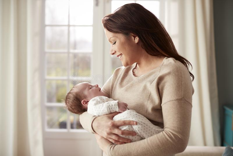 Liebevolle Mutter, die zu Hause neugeborenes Baby streichelt lizenzfreie stockfotos