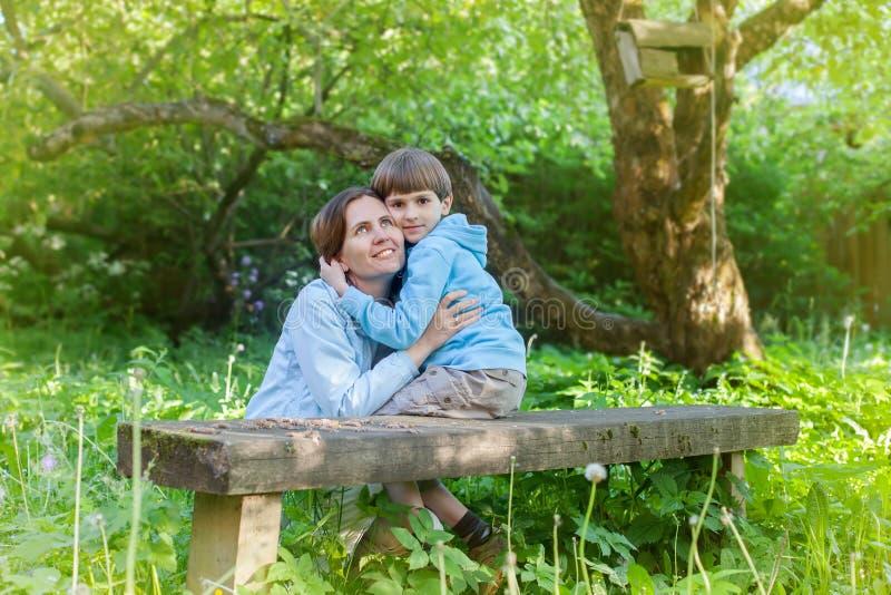 Liebevolle Mutter mit ihrem kleinen Sohn auf einer Bank lizenzfreies stockbild