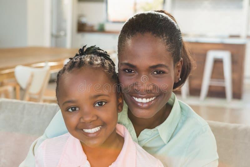 Liebevolle Mutter mit Tochter auf der Couch lizenzfreie stockbilder