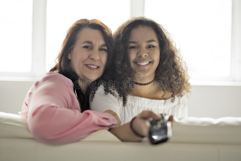 Liebevolle Mutter und Tochter, die im hörendem Fernsehen des Sofas mit Direktübertragung sitzt lizenzfreie stockfotos