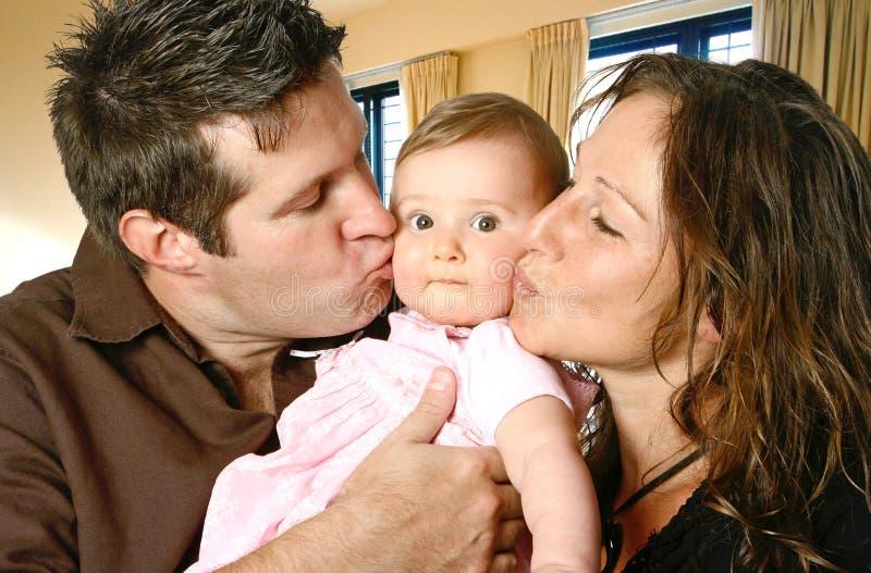 Liebevolle Mutter und Vater, die ihr Baby küßt stockbild