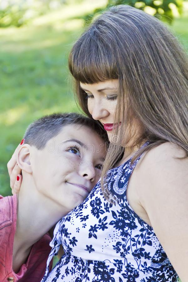 Liebevolle Mutterumarmungen mit Jugendlichsohn stockfotos