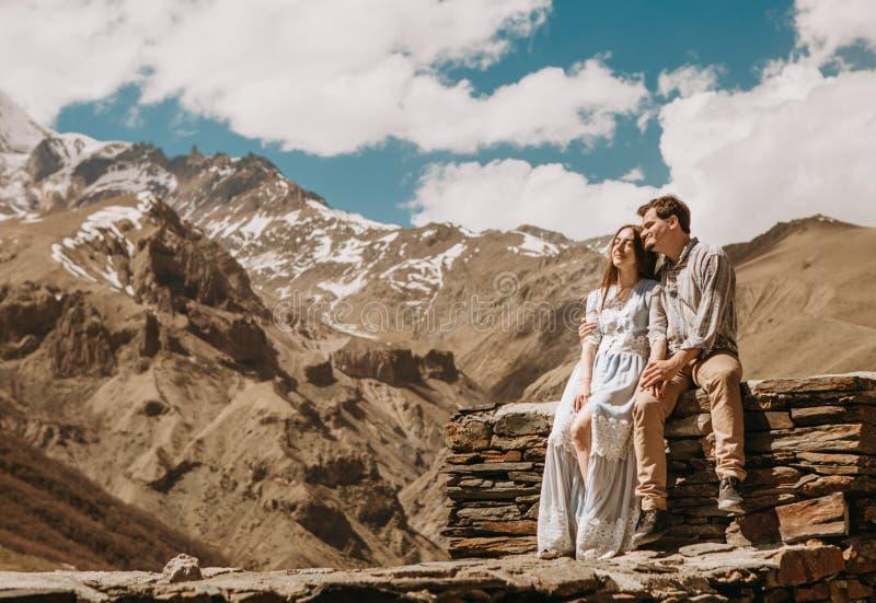 Liebevolle Paarberge, die sitzenden Steinzaun träumend aufpassen lizenzfreies stockbild