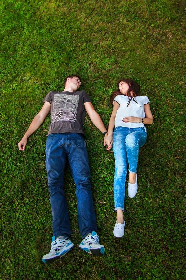 Liebevolle Paare auf dem Graslügen lizenzfreies stockbild