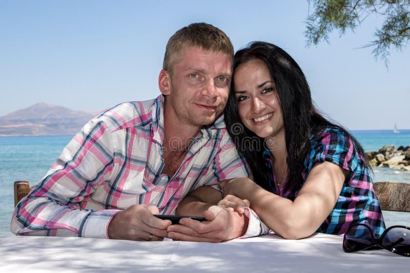 Liebevolle Paare auf Seehintergrund lizenzfreie stockfotos