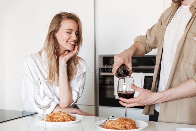 Liebevolle Paare in der Küche haben einen trinkenden Wein des Abendessens, der Spaghettis isst lizenzfreie stockfotografie