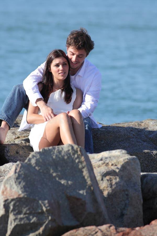 Liebevolle Paare, die auf einem Stein auf dem Strand flirten und umarmen stockbilder