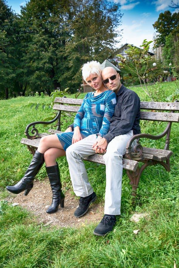 Liebevolle Paare, die auf einer Parkbank sitzen lizenzfreie stockfotos