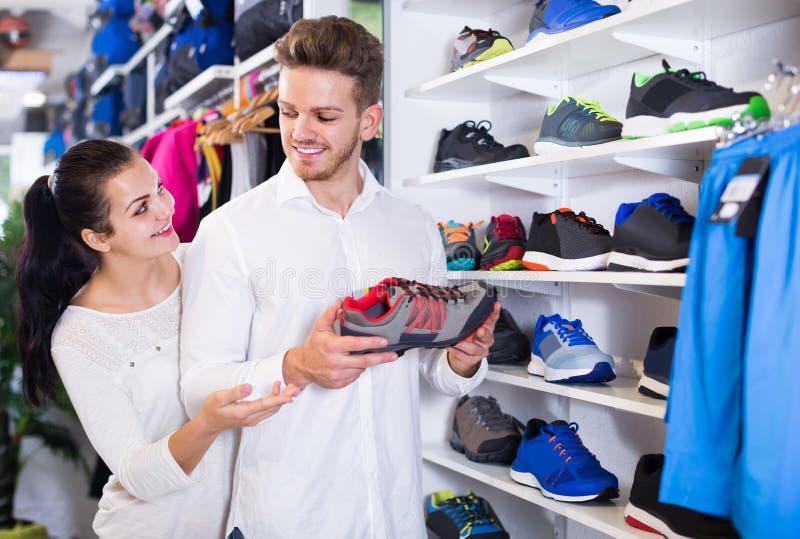 Liebevolle Paare, die auf neuen Turnschuhen im Sportspeicher entscheiden lizenzfreie stockbilder