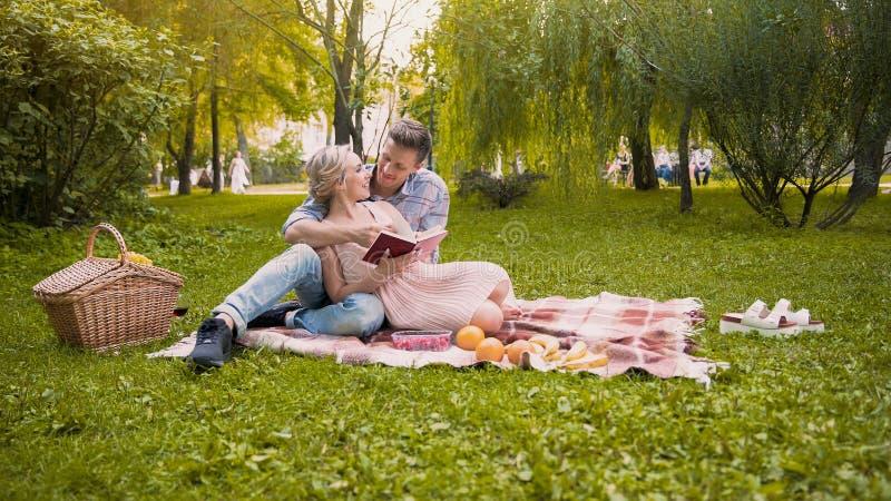 Liebevolle Paare, die das Buch, sitzend auf Wolldecke während des Picknicks, romantisches Datum besprechen lizenzfreie stockbilder
