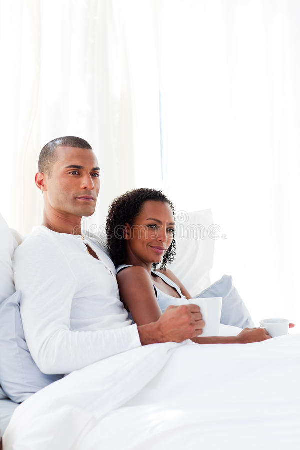Liebevolle Paare, die einen Kaffee auf ihrem Bett trinken lizenzfreie stockfotografie