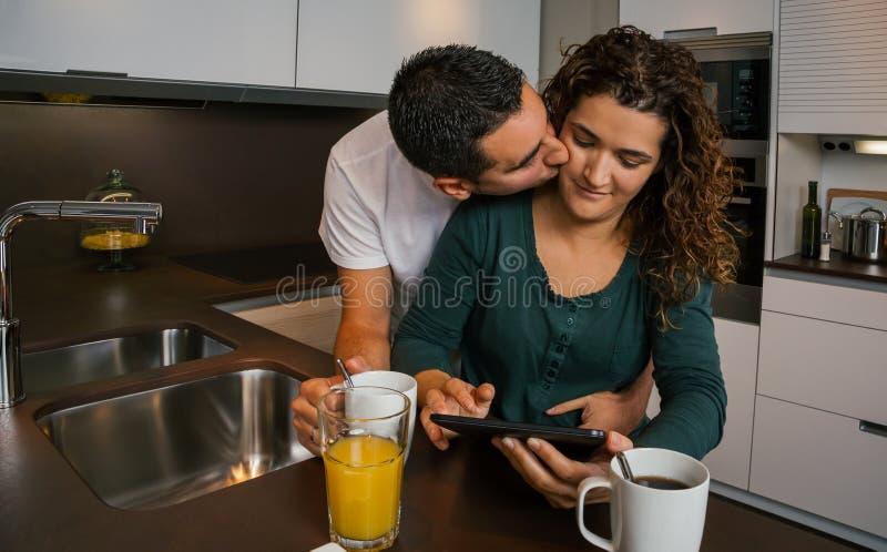 Liebevolle Paare, die frühstücken und Tablette schauen lizenzfreie stockfotos