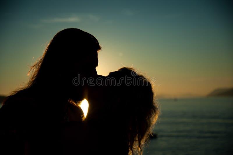 Liebevolle Paare, die im Sonnenuntergang am Strand küssen stockbilder