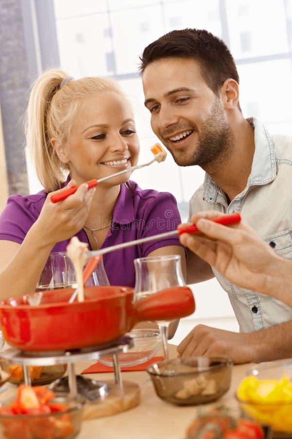 Liebevolle Paare, die Käsefondue essen lizenzfreie stockfotografie