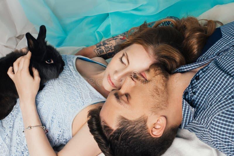 Liebevolle Paare, die nahe dem Fenster mit einem Kaninchen auf seinen Händen liegen Zarte und romantische Gefühle der Jungvermähl stockbilder