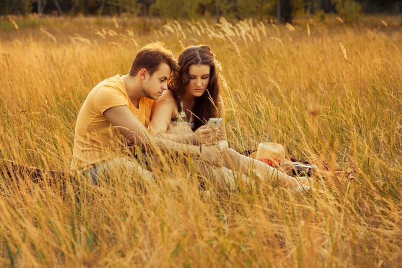 Liebevolle Paare, die sich auf Blumenfeld im herbstlichen Park, warm hinlegen stockfotografie