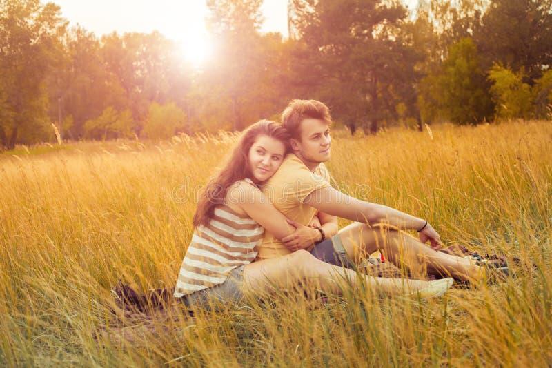 Liebevolle Paare, die sich auf Blumenfeld im herbstlichen Park, warm hinlegen stockfoto