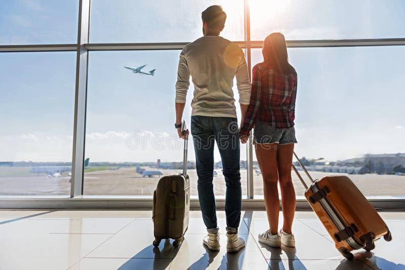 Liebevolle Paare Dreamful, die Fliegenflugzeug betrachten lizenzfreie stockfotos