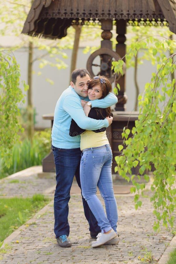 Liebevolle Paare am hölzernen Brunnen lizenzfreies stockbild