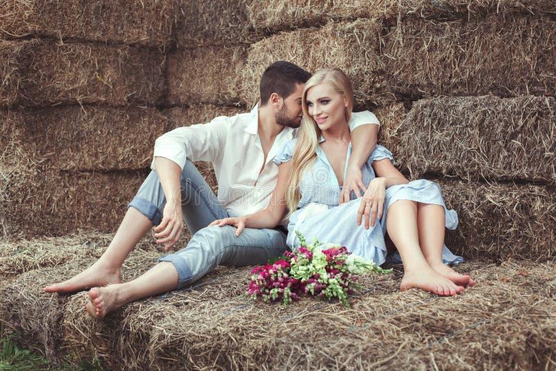 Liebevolle Paare haben im Ruhestand auf einem Mähung stockfotografie