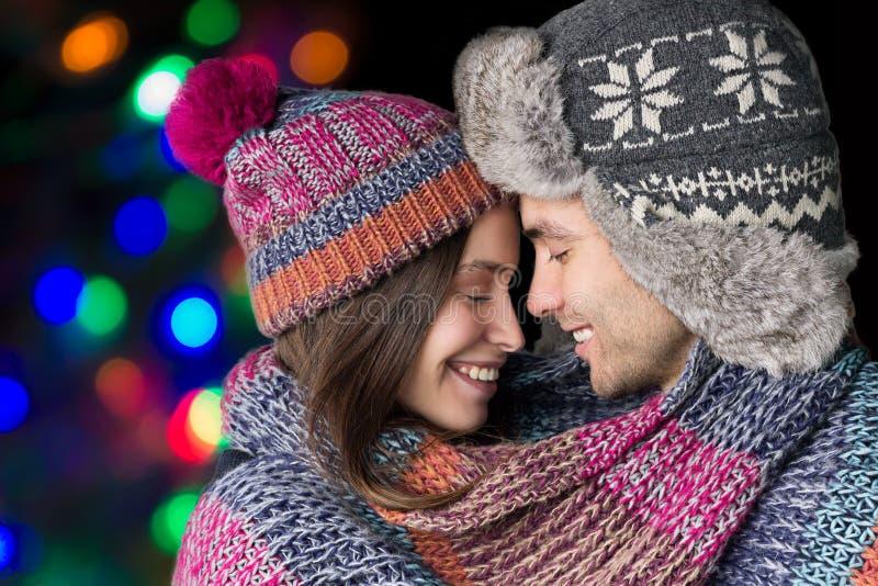 Liebevolle Paare in warmem kleiden Weihnachtsniederlassung und -glocken stockfotos