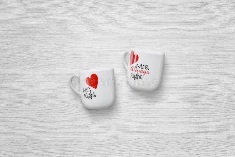 Liebevolle Paarschalen auf weißem Holztisch mit freiem Raum für Text lizenzfreies stockfoto