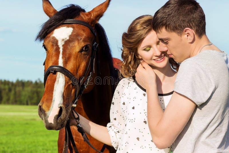 Liebevolle schöne Paare von Kerlen und von Mädchen auf dem Gebiet gehen auf Pferde stockfotografie