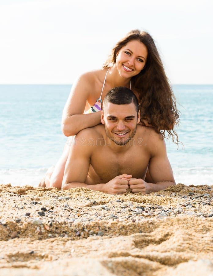 Liebevoller Mann und seine Freundin auf Sand setzen auf den Strand stockfotografie